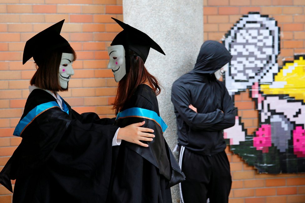 University students wearing Guy Fawkes masks pose for a photoshoot