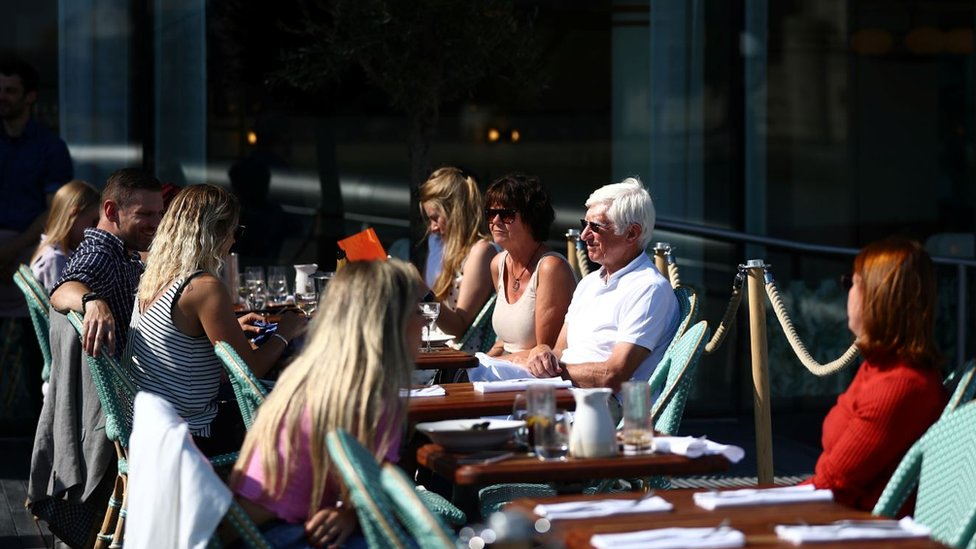 People eating at restaurant tables outdoors