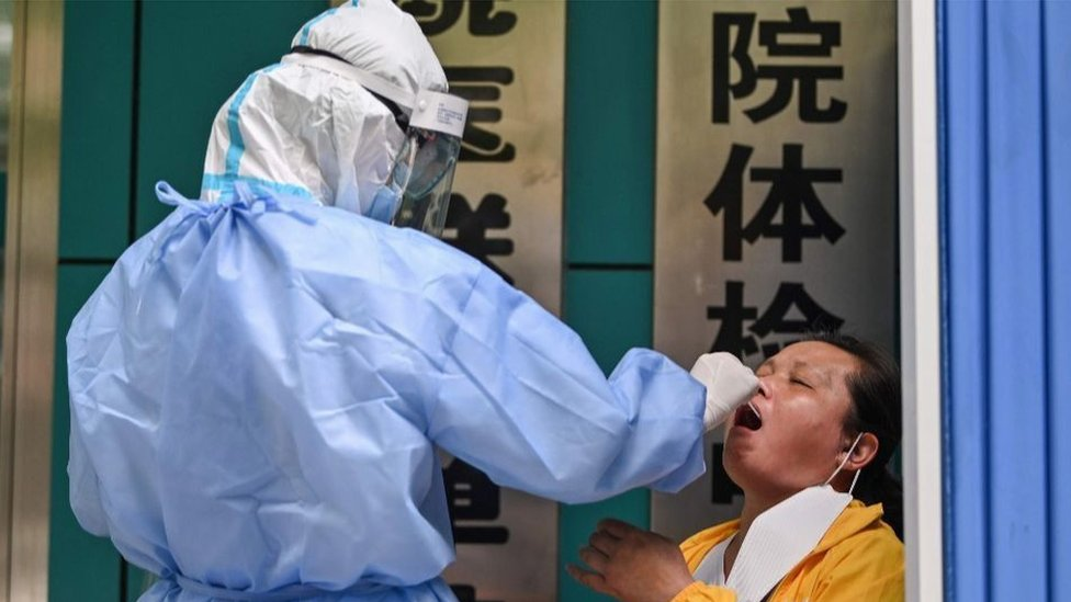 A medical worker takes a swab sample from a woman to be tested for the COVID-19 novel coronavirus in Wuhan, in Chinas central Hubei province on May 13, 2020.