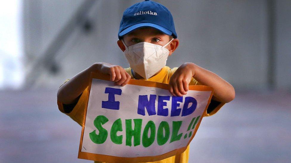 """Un niño sostiene un cartel con la frase en inglés: """"I need school"""" (necesito escuela)"""