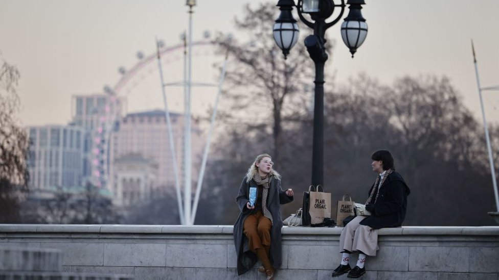 Two people sitting on a wall talking