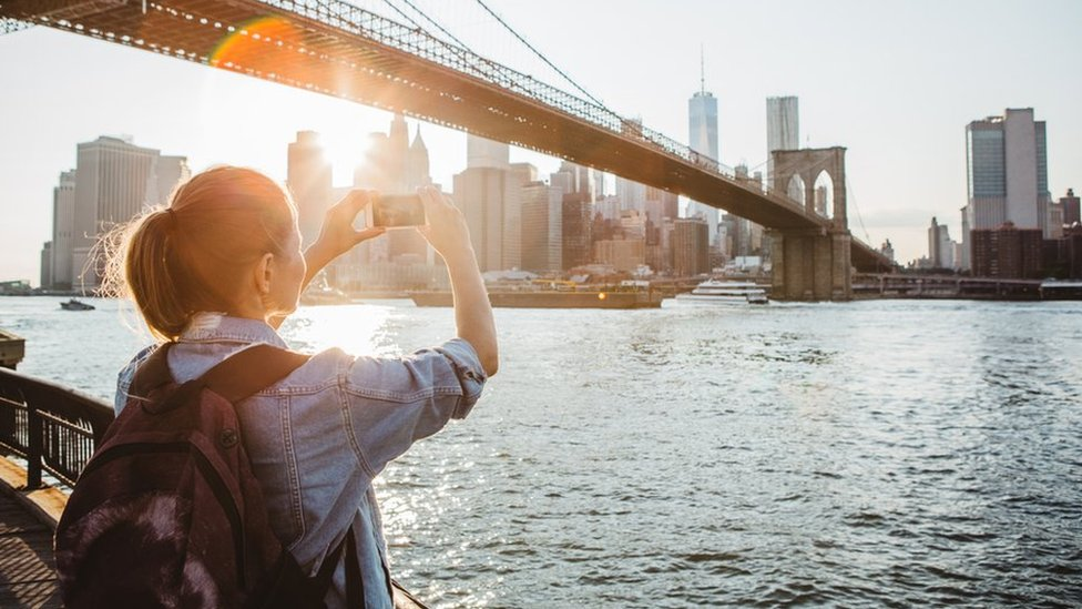 A woman takes a picture in New York
