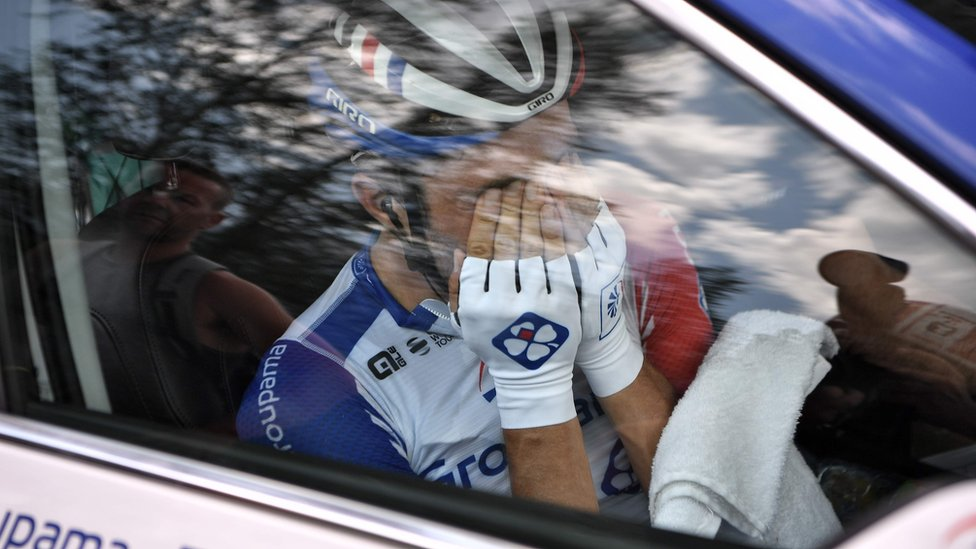 France's Thibaut Pinot, in his team car, reacts after quitting the Tour