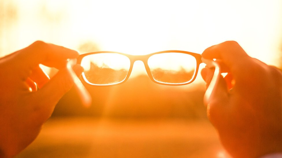 A person holding glasses against the sun