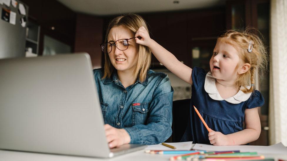 Una mujer intenta trabajar mientras su hija le quita los anteojos