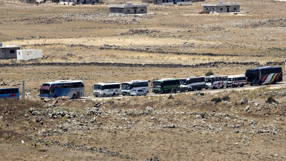 Syrian rebels and families gather to leave at the village of al-Qahtaniah, next to the city of Quneitra, at the Syrian part of the Golan Heights, as seen from the Israeli side of the border, 20 July 2018