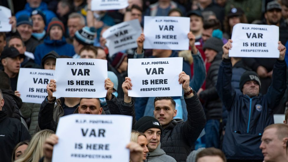 "Fans hold up signs saying ""VAR is here"""