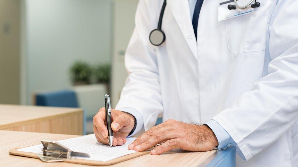 Médico escribiendo