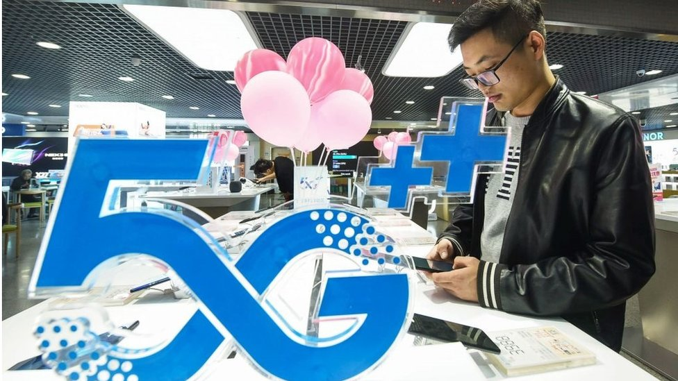 A customer looks at a mobile phone next to a 5G logo at a store in Hangzhou in China's eastern Zhejiang province on October 31, 2019