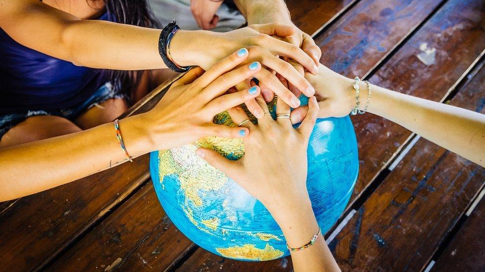 prijatelji drže globus
