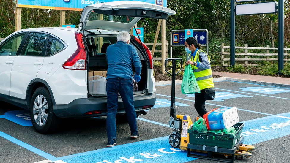 Aldi customer Clive Perkins loads groceries into his car with the help of an Aldi staff member