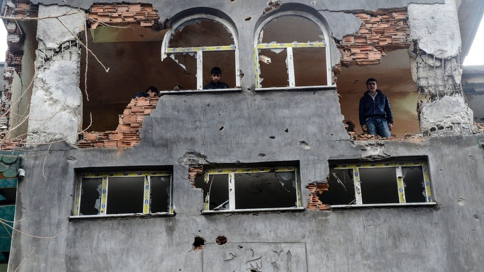 A man stands in a building damaged by fighting between Turkish government forces and Kurdish rebels in the southeastern city of Silopi in January 2016.