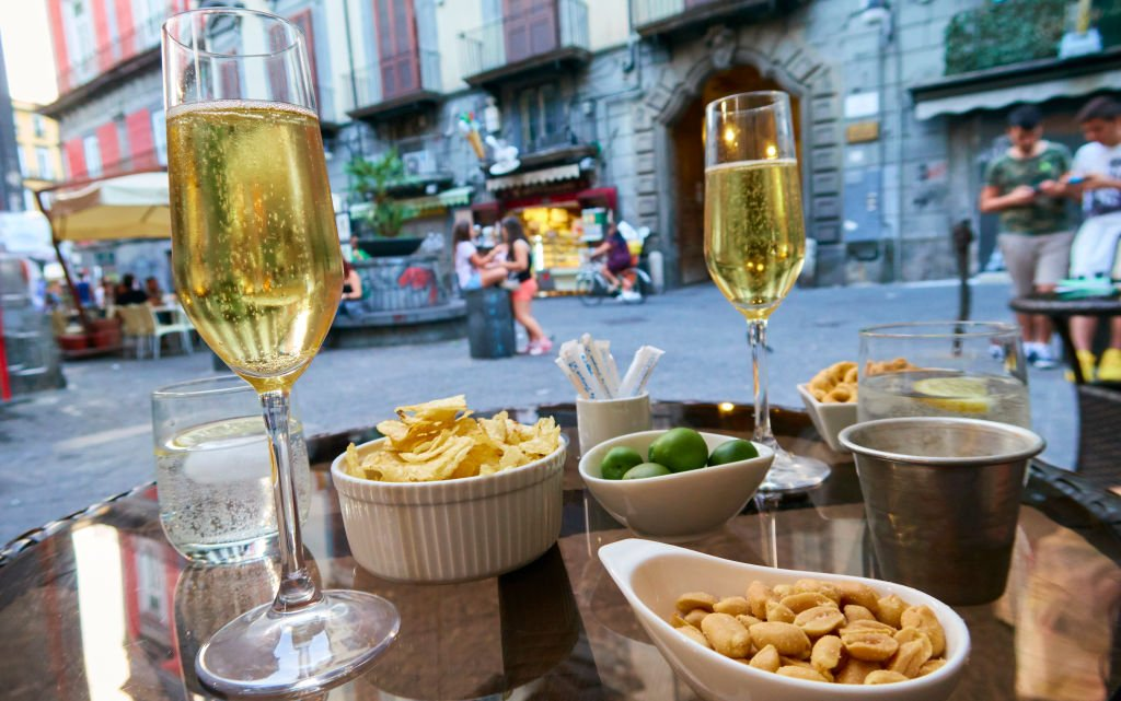 An outside table at a restaurant with champagne and plates with crisps, olives and peanuts