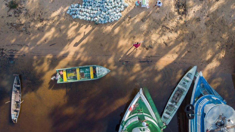 Vista aérea de kits de limpeza sendo entregues em comunidade à beira do rio