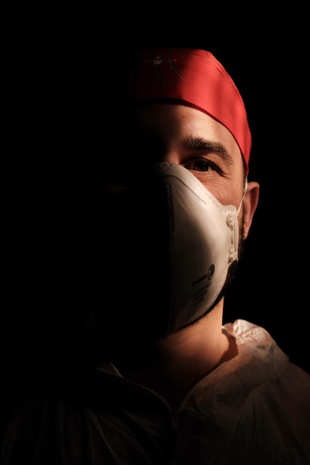 A male nurse wearing a face mask with a dark background behind him.