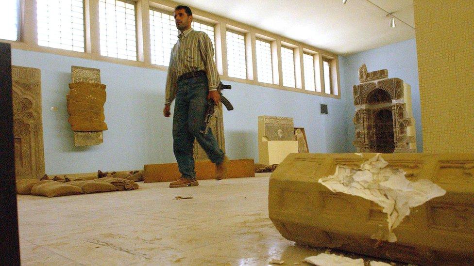 Man with gun walks through looted museum