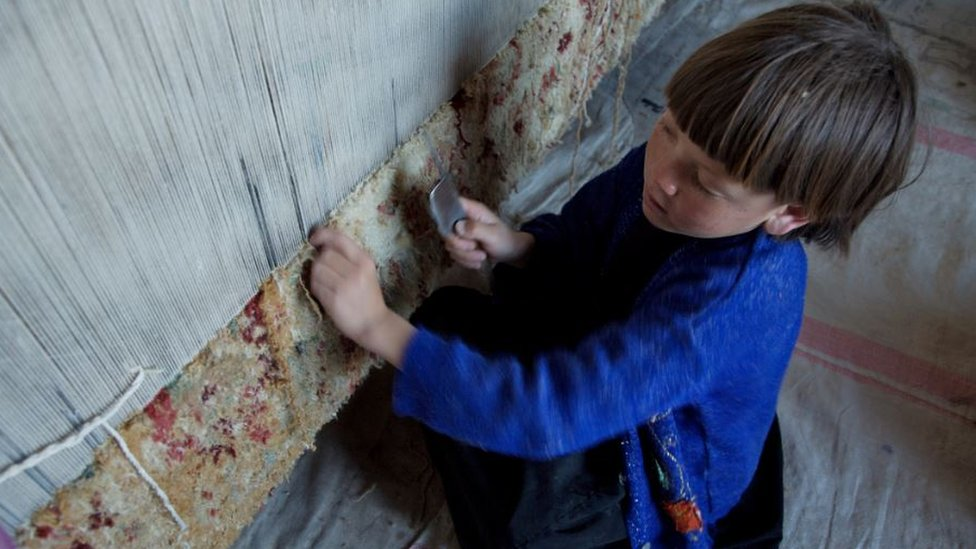 An eight-year-old child weaving a carpet