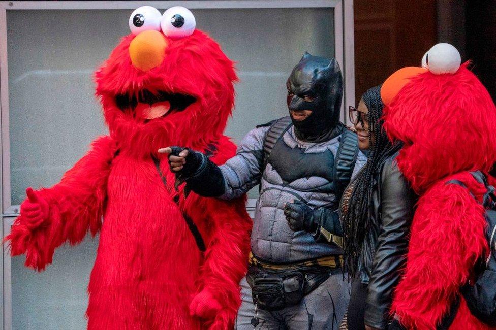 Un hombre disfrazado de Batman y otras dos personas de Elmo en Nueva York en noviembre de 2019.