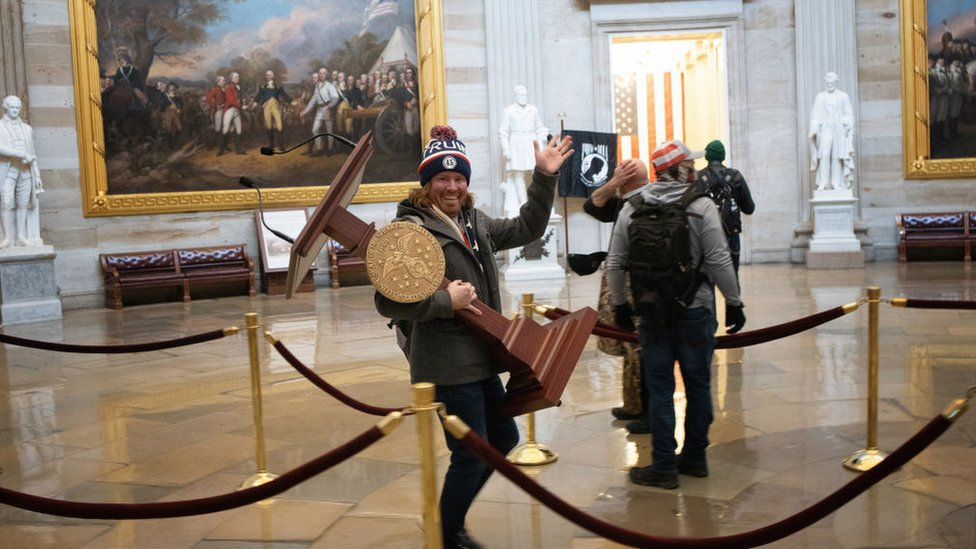 A man is pictured carrying the lectern from the House of Representatives