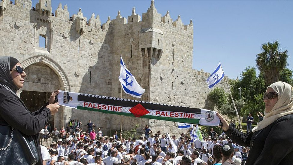 "Palestinian women hold ""Palestine"" scarf as Israeli youth dance outside walls of Old City in Jerusalem (file photo)"