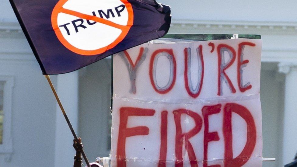 "A flag and a ""you're fired banner"" in front of the White House"