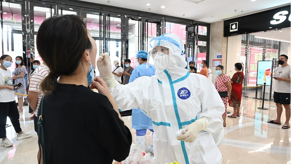 A medical worker collects a throat swab from a staff member for nucleic acid testing at Wanda Plaza on September 11, 2021 in Putian, Fujian Province of China.