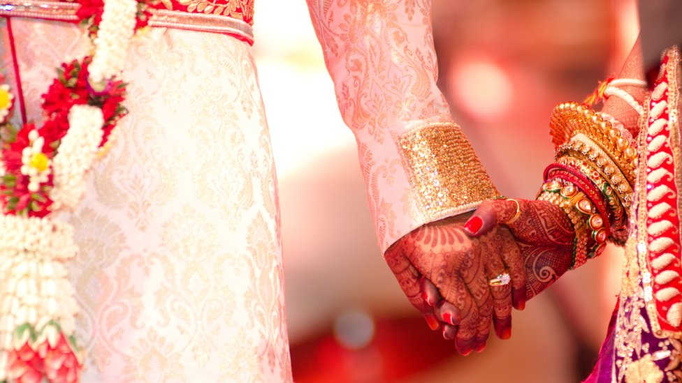 Groom holding henna decorated hand of bride (generic image)