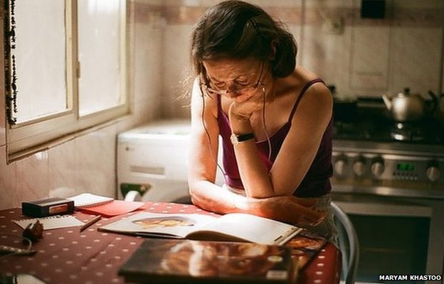 Mum reading cookery books in the afternoon light after a long day at work