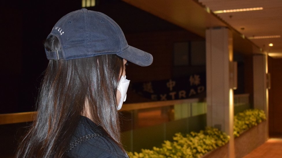 """Side view of """"Jackie"""", a student protester, wearing a cap and mask"""