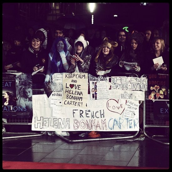 Helena Bonham Carter fans at a premiere, holding posters and autograph books