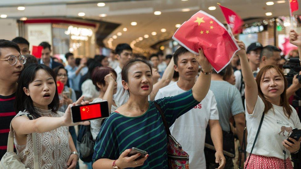 有持中國國旗的人不滿示威者在商場聚集。