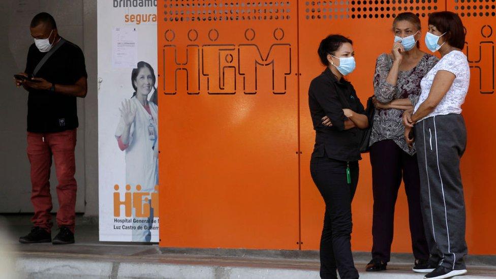 Personas con mascarillas en las afueras de un hospital en Medellín.