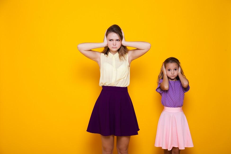 Dos niñas se cubren las orejas.