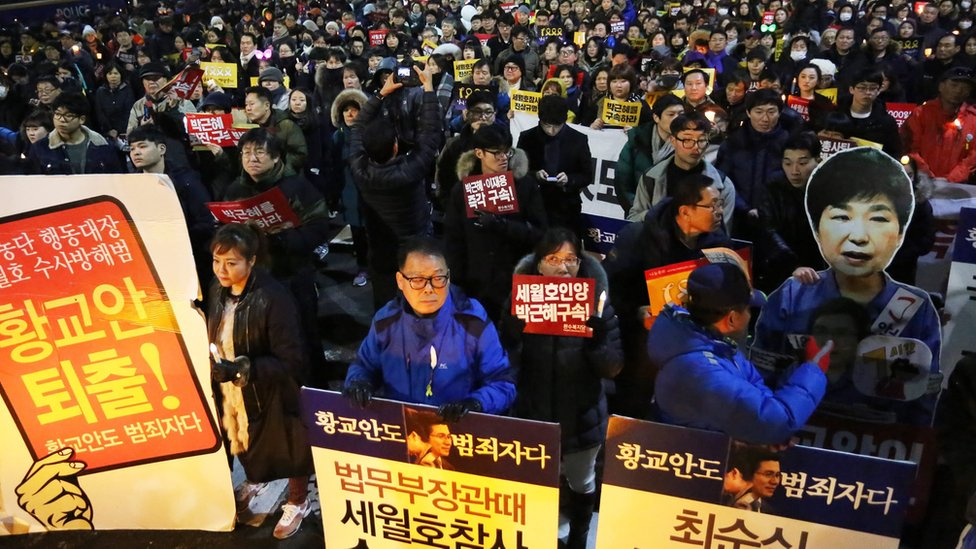 韓國首爾示威者手持「朴槿惠與黃教安下台」的紙板(7/1/2017)
