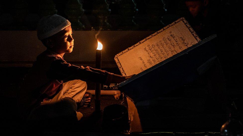 Dečak čita pod svetlošću zapaljenih baklji