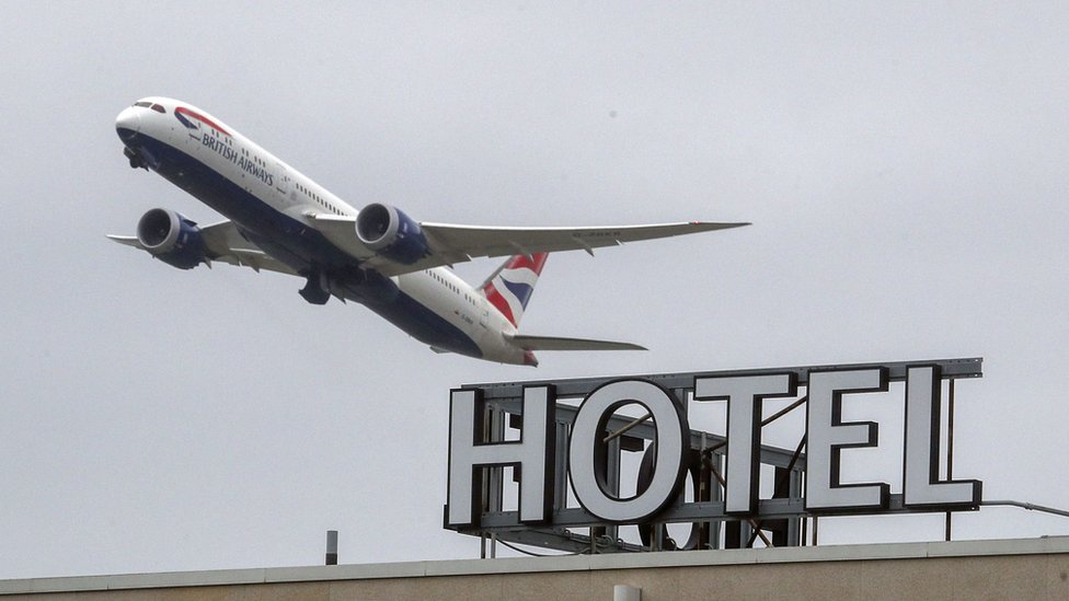 A plane passing over a hotel at Heathrow