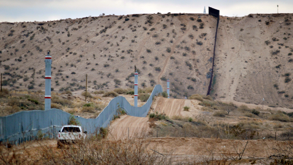 A US Border Patrol agent drives near the US-Mexico border fence in Sunland Park, New Mexico