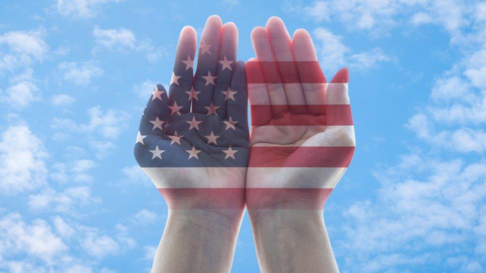 Manos con la bandera estadounidense que apuntan al cielo.