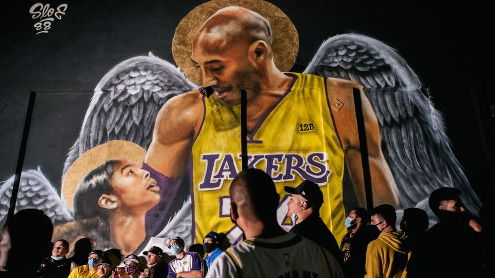 Lakers fans celebrate near a mural of Kobe Bryant and his daughter Gianna