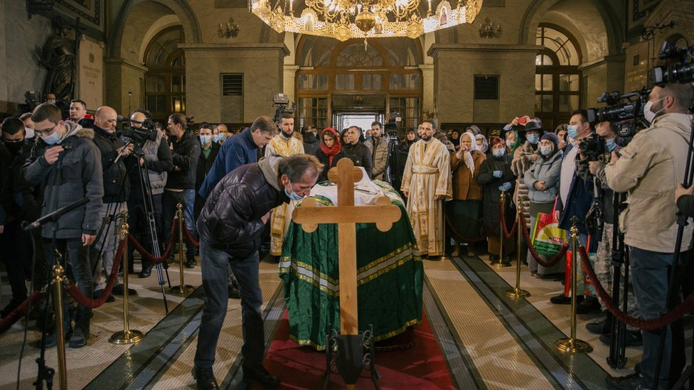 An orthodox faithfhul bends on the cross near the casket of late Serbian patriarch Irinej during his funeral service at Belgrade's cathedral on November 21, 2020 in Belgrade, Serbia.