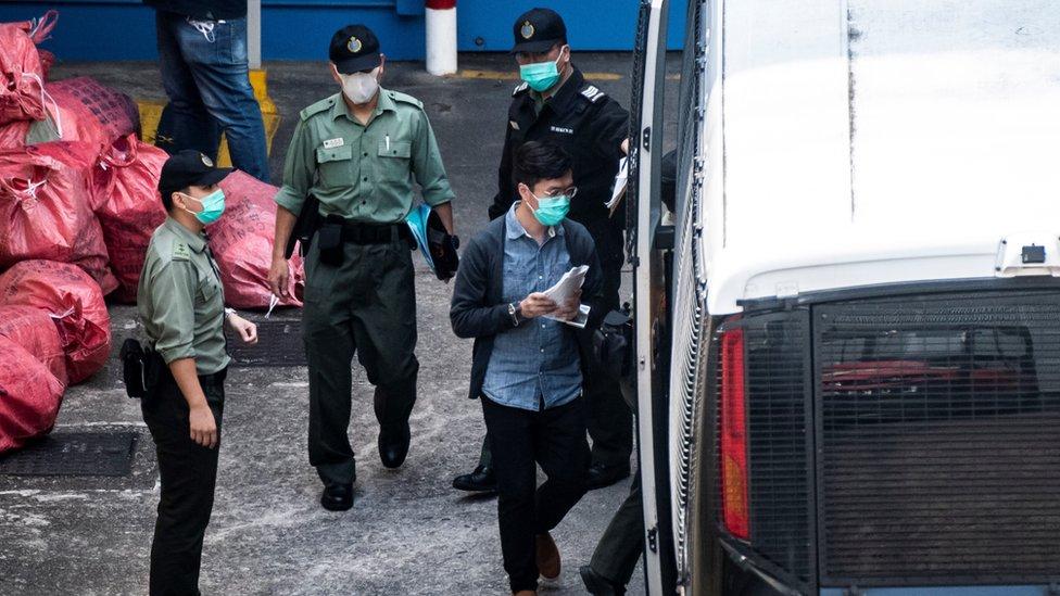 前香港立法會議員區諾軒(圖中藍色上衣者)在九龍荔枝角收押所被押上囚車(2/3/2021)