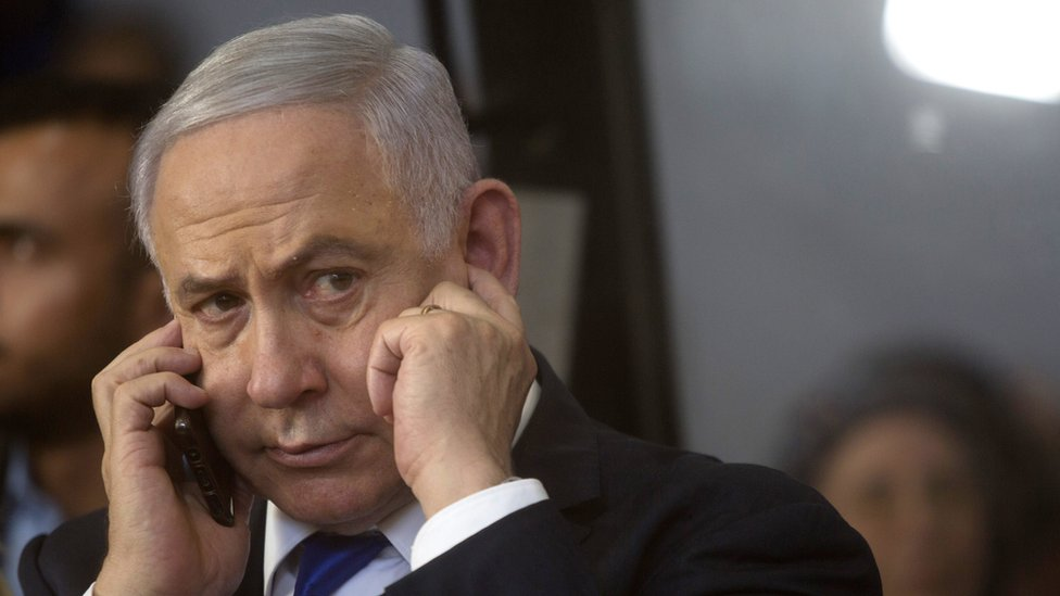 Benjamin Netenyahu puts a figner in his ear while listening intently to a phone call