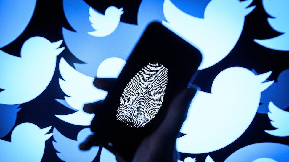 Telefon na čijem je ekranu otisak prsta, u pozadini logo Tvitera