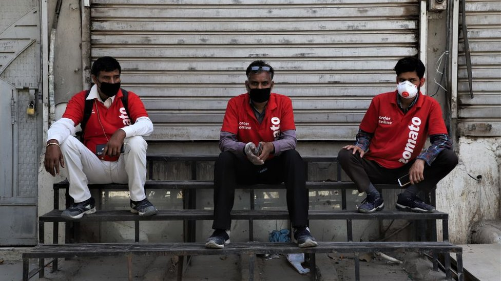 Zomato Food Delivery boys wearing protective masks sit near closed shutters amid Covid-19 (Coronavirus) lock down in Gurugram on the Outskirts of New Delhi, India on 07 April 2020.