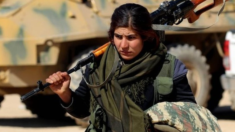 A female Kurdish fighter of the US-backed Syrian Democratic Forces (SDF), made up of an alliance of Arab and Kurdish fighters, walks carrying a weapon in the village of Sabah al-Khayr on the northern outskirts of Deir Ezzor as they advance to encircle the Islamic State (IS) group bastion of Raqa on 21 February 2017.