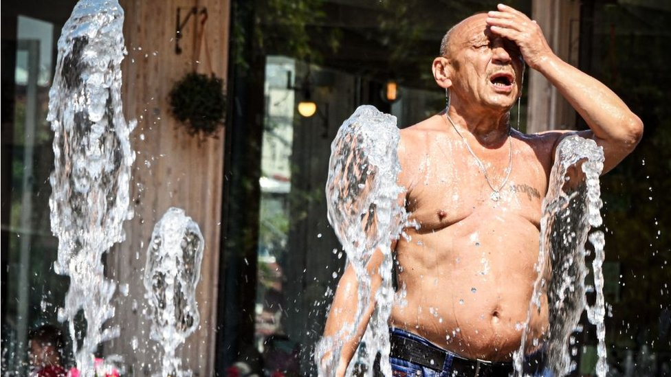 Hombre refrescándose en una fuente en Moscú