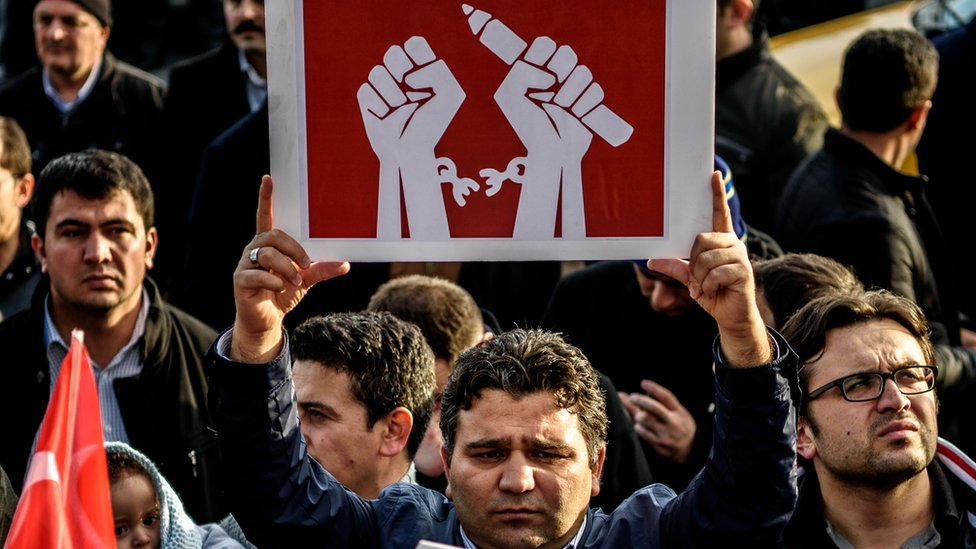 A man holds up a placard as people demonstrate in support of Turkish daily newspaper Zaman in Istanbul on 4 March 2016