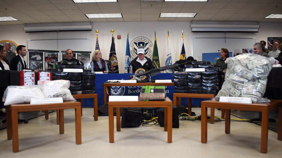 Trump memberikan keterangan di antara tumpukan senjata, uang, dan obat-obatan terlarang yang disita oleh patroli petugas perbatasan AS pada 10 Januari 2019