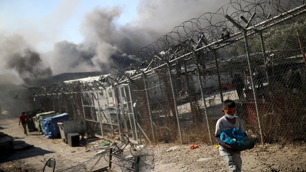 A child walks among destroyed shelters following a fire at the Moria camp for refugees and migrants on the Island of Lesbos, Greece 9 September 2020