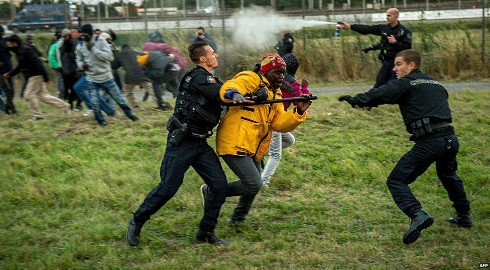 French police drive off migrants seeking to enter the Eurotunnel site in Calais